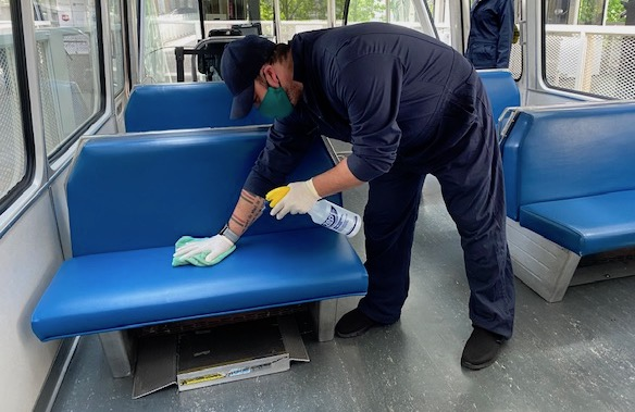 employee cleaning seats on train